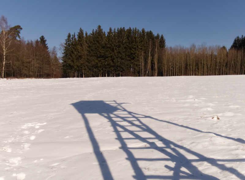 Der Schatten eines Hochsitzes im Schnee